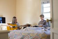 Caucasian lesbian couple relaxing in bedroom 11018071770| 写真素材・ストックフォト・画像・イラスト素材|アマナイメージズ