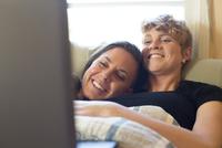 Caucasian lesbian couple cuddling in bed 11018071772| 写真素材・ストックフォト・画像・イラスト素材|アマナイメージズ