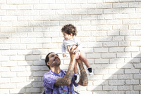 Father playing with baby son outdoors 11018071793| 写真素材・ストックフォト・画像・イラスト素材|アマナイメージズ