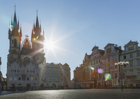 Sun shining behind ornate church in city square