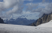 Hikers walking on glacier in remote landscape