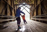 Caucasian mother and baby daughter on covered bridge