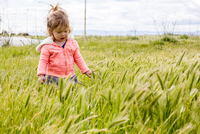 Caucasian baby girl playing in field