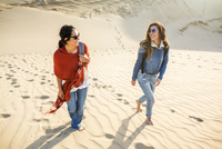 Mixed race women walking on sand dunes
