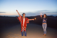 Mixed race women playing with sparklers on sand dunes