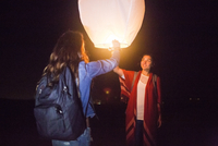 Mixed race women floating lantern at night