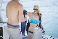 Caucasian divers holding flippers on boat 11018071965| 写真素材・ストックフォト・画像・イラスト素材|アマナイメージズ