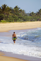 Mixed race surfer carrying surfboard on beach