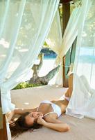 Pacific Islander woman laying in cabana