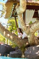 Pacific Islander woman sitting in tree near cabana