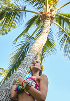 Pacific Islander woman standing under palm tree
