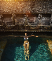 Pacific Islander woman floating in ornate pool