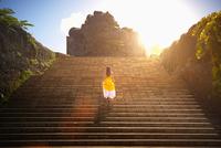 Pacific Islander woman walking on monument steps