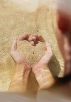 Pacific Islander woman holding handful of sand