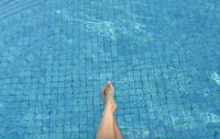 Pacific Islander woman dangling feet in swimming pool