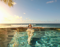 Pacific Islander woman laying in swimming pool