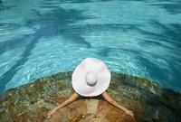 Pacific Islander woman laying in swimming pool