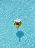 Pacific Islander woman floating in swimming pool