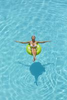 Pacific Islander woman floating in swimming pool