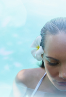 Pacific Islander woman in pool with flower in her hair
