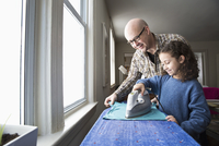 Father teaching daughter to iron fabric