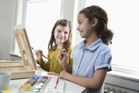 Smiling girls painting
