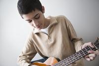 Mixed race teenage boy playing guitar 11018072134| 写真素材・ストックフォト・画像・イラスト素材|アマナイメージズ
