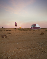 Woman camping in remote desert field