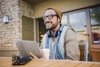 Hispanic man reading digital tablet at coffee shop