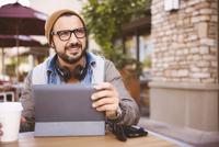Hispanic man using digital tablet at coffee shop