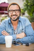 Hispanic man drinking coffee at coffee shop 11018072211| 写真素材・ストックフォト・画像・イラスト素材|アマナイメージズ