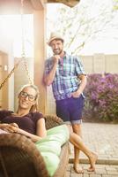 Hispanic couple smiling on porch
