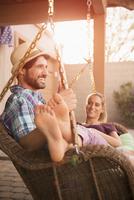 Hispanic couple relaxing in porch swing