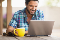 Hispanic man using laptop and drinking coffee outdoors