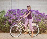 Hispanic woman standing on bicycle