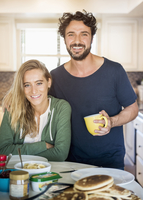 Hispanic couple smiling in kitchen