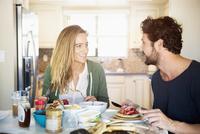 Hispanic couple eating in kitchen