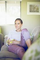 Hispanic woman drinking coffee on sofa