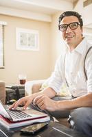 Hispanic man using laptop on sofa 11018072251| 写真素材・ストックフォト・画像・イラスト素材|アマナイメージズ