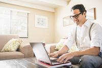 Hispanic man using laptop on sofa 11018072252| 写真素材・ストックフォト・画像・イラスト素材|アマナイメージズ