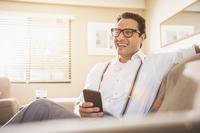 Hispanic man using cell phone on sofa 11018072254| 写真素材・ストックフォト・画像・イラスト素材|アマナイメージズ