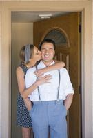 Hispanic couple kissing in doorway