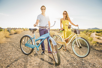 Hispanic couple standing with bicycles on dirt road