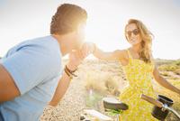 Hispanic man kissing hand of girlfriend on dirt road