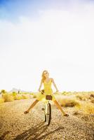 Hispanic woman riding bicycle on dirt road 11018072265| 写真素材・ストックフォト・画像・イラスト素材|アマナイメージズ