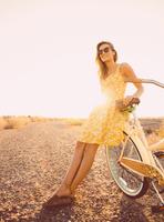 Hispanic woman leaning on bicycle on dirt road 11018072272| 写真素材・ストックフォト・画像・イラスト素材|アマナイメージズ