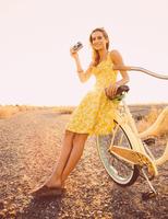 Hispanic woman photographing with bicycle on dirt road 11018072274| 写真素材・ストックフォト・画像・イラスト素材|アマナイメージズ