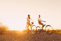 Blurred view of Hispanic couple riding bicycles on dirt road