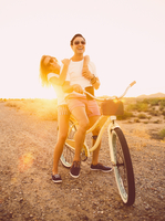 Hispanic couple riding bicycle on dirt road