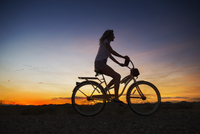 Silhouette of Hispanic woman riding bicycle at sunset